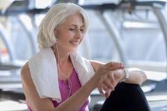 Femme avec plaisir heureuse souriant et regardant la montre Photographie stock