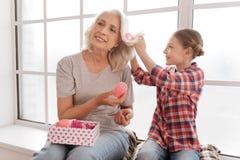 Femme avec plaisir positive tenant une boîte avec des rouleaux de cheveux Photographie stock libre de droits