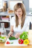 Femme avec plaisir préparant un repas sain Photographie stock libre de droits