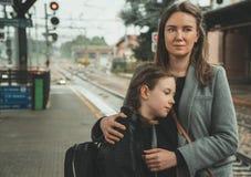 Femme avec sa fille sur la gare ferroviaire image stock