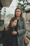 Femme avec sa fille sur la gare ferroviaire photographie stock