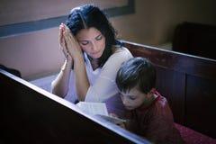 Femme avec sa prière de fils Images stock
