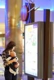 Femme avec son bébé dans un centre commercial Photographie stock libre de droits