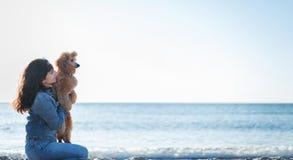 Femme avec son chien à la plage arénacée de mer Images libres de droits