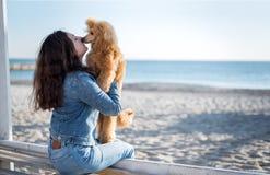 Femme avec son chien à la plage arénacée de mer Photos stock
