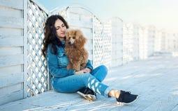 Femme avec son chien à la terrasse en bois sur la plage de mer Images stock