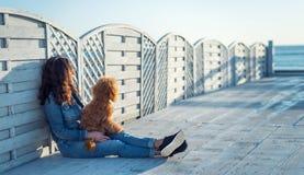 Femme avec son chien à la terrasse en bois sur la plage de mer Image libre de droits