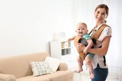 Femme avec son fils dans le transporteur de bébé à la maison photos libres de droits