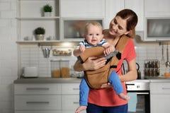 Femme avec son fils dans le transporteur de bébé à la maison photographie stock