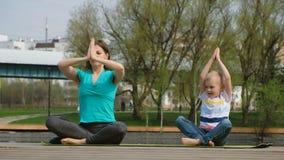 Femme avec son fils faisant le yoga par l'étang, dehors clips vidéos