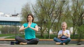 Femme avec son fils faisant le yoga par l'?tang, dehors clips vidéos