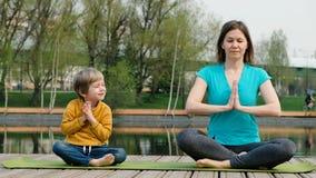 Femme avec son fils faisant le yoga par l'?tang, dehors banque de vidéos