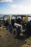 Femme avec SUV à la plage Photo stock