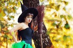 Femme avec un balai à disposition et un chapeau de sorcières Photographie stock
