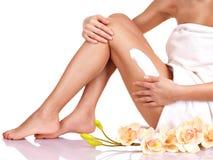 Femme avec un beau avec le corps de fleurs employant une crème Photographie stock