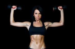 Femme avec un beau corps avec des haltères Photo stock