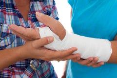 Femme avec un bras cassé et son travailleur social Image libre de droits
