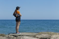 Femme avec un chapeau contre le soleil se tenant sur les roches du Br Photographie stock