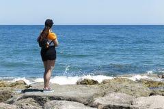 Femme avec un chapeau contre le soleil se tenant sur les roches du Br Photographie stock libre de droits