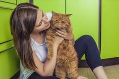 Femme avec un chat de gingembre dans des ses bras caressant sur la cuisine photos stock