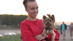 Femme avec un chien dans des ses bras banque de vidéos