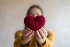 Femme avec un coeur à crochet photos stock