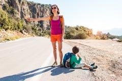 Femme avec un enfant faisant de l'auto-stop photos stock