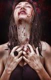Femme avec un long cou, de belles épaules, des cheveux humides, une expression tragique sur son visage et une goutte de sang photographie stock libre de droits