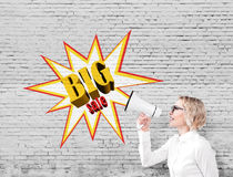 Femme avec un mégaphone près d'une grande affiche de vente sur un mur de briques Images stock