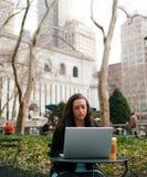 Femme avec un ordinateur en stationnement Photographie stock