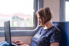 Femme avec un ordinateur portable sur le train Image libre de droits