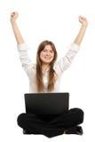 Femme avec un ordinateur portatif appréciant sa réussite en ligne Photo stock
