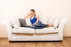 Femme avec un ordinateur portatif sur un salon photographie stock