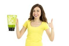 Femme avec un pot de smoothie vert renonçant à des pouces Photographie stock libre de droits