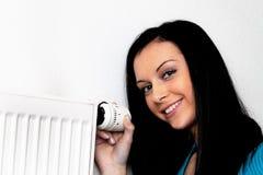 Femme avec un radiateur et un thermostat de chauffage Photographie stock libre de droits