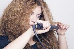 Femme avec un redresseur de cheveux Photo stock