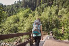 Femme avec un sac à dos entrant sur un pont dans la forêt photographie stock libre de droits