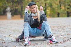 Femme avec un sourire mignon se reposant sur le panneau de patin Image libre de droits