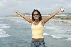 Femme avec un téléphone à la plage Photo libre de droits