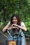 Femme avec un vélo souriant à l'extérieur Photographie stock libre de droits