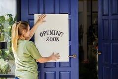 Femme avec une ouverture bientôt du signage Photographie stock