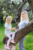Femme avec une petite fille marchant par Apple de floraison photo stock