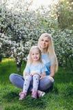Femme avec une petite fille marchant par Apple de floraison photographie stock libre de droits