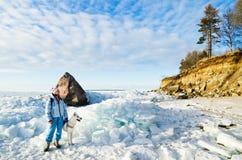 Femme avec une promenade de chien un jour ensoleillé d'hiver Photographie stock