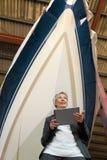 Femme avec une Tablette devant un bateau dans un chantier naval Photo stock