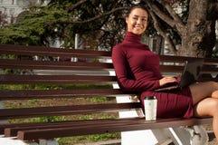 Femme avec une tasse d'orthographe de cofee sur le carnet Images stock