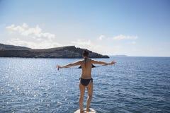 Femme aventureuse enlevant le maillot de bain environ pour sauter Images stock