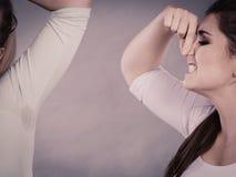 Femme ayant l'aisselle humide sa puanteur sentante d'ami Photographie stock libre de droits
