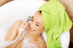 Femme ayant l'amusement avec le showerhead Photo stock