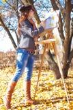 Femme ayant l'amusement riant près du chevalet Photo libre de droits